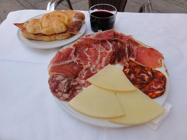 Tabla_de_embutidos_y_queso,_chato_de_vino_y_bocadillo_de_jamón